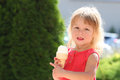 Little girl eating ice cream outdoors a Stock Photography