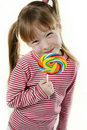 Little girl eating a lollipop Stock Images