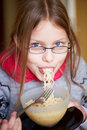 Little girl eating noodles Stock Images