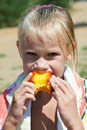 Little girl eating a peach Stock Image