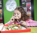Little girl eating pizza the with long hair in a pink jacket in a pizzeria eats a Royalty Free Stock Photos