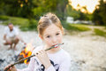 Little girl eating roasted marshmallow Royalty Free Stock Photo