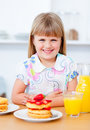 Little girl eating waffles with strawberries Stock Photography