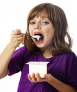 Little girl eating a yogurt Royalty Free Stock Images