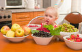 The little girl eats a berry Royalty Free Stock Photos