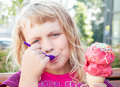 Little girl eats big fruit ice-cream Royalty Free Stock Photos