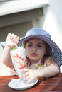 Little girl eats ice cream from a tall glass Stock Photo