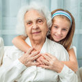 Little girl embracing grandmother smiling Royalty Free Stock Photos
