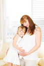 Little girl embracing her pregnant mother feeling s belly Stock Photography