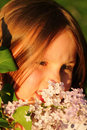 Little girl enjoying flowers beautiful lilac Stock Photography