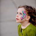 Little girl with face paint pretty blue eyes wearing green shirt Royalty Free Stock Photo