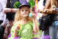 A little girl in fancy green dress blow soap bubbles on the holiday of spring and Stock Image