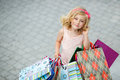 Little girl fashion with packages at the mall in a large shopping center pretty smiling shopping bags posing in shop Royalty Free Stock Photography