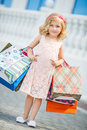 Little girl fashion with packages at the mall in a large shopping center pretty smiling shopping bags posing in shop Royalty Free Stock Images