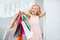 Little girl fashion with packages at the mall in a large shopping center pretty smiling shopping bags posing in shop Stock Image