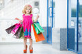 Little girl fashion with packages at the mall in a large shopping center pretty smiling shopping bags thumb up sign in Royalty Free Stock Images