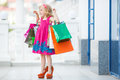 Little girl fashion with packages at the mall in a large shopping center pretty smiling shopping bags thumb up sign in Stock Image