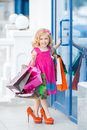 Little girl fashion with packages at the mall in a large shopping center pretty smiling shopping bags thumb up sign in Royalty Free Stock Photography