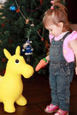 Little girl feeding carrot toy donkey Royalty Free Stock Photo