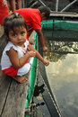 Little girl feeding fish, Thailand Royalty Free Stock Photography