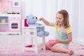 Little girl feeding her toy bear Royalty Free Stock Photo