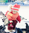 Little girl feeding pigeons with hands Royalty Free Stock Photo