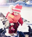 Little girl feeding pigeons in winter