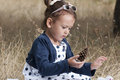 Little girl in field with pine cone young child sitting a outdoors looking at a wonder Royalty Free Stock Photography