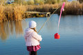 Little girl fishing from dock on lake. Royalty Free Stock Photo