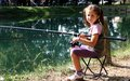 Little girl with the fishing rod on the shores of Lake fishing 1 Royalty Free Stock Photo