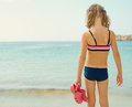 Little girl with flip flops standing on the beach Stock Image