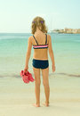 Little girl with flip flops standing on the beach Royalty Free Stock Photo