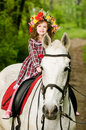 Little girl in floral wreath riding horse Royalty Free Stock Photo