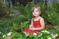 Little girl in flower bed Royalty Free Stock Images