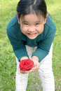 Little girl with flower headband holding red rose in hands. Royalty Free Stock Photo