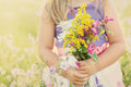 Little girl with flowers on grassy meadow holding wild bouquet a sunny summer field Royalty Free Stock Photography