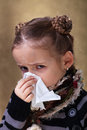Little girl flu season wearing warm clothes blowing nose Royalty Free Stock Photos
