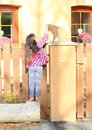 Little girl fondling a cat barefoot kid orrange on column of wooden fence Royalty Free Stock Photo