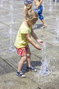 Little girl at the fountains playing fun Stock Photography