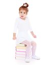 Little girl froze while sitting on a stack of books isolated white background lotus children s center Royalty Free Stock Photos