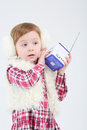 Little girl in fur headphones holds portable radio on white background Royalty Free Stock Image