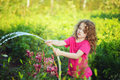Little girl  gardening on sunny day watering flower in the garde Royalty Free Stock Photo