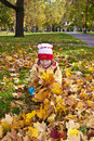 Little girl gathering autumn leaves Stock Photo