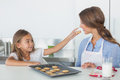 Little girl giving a cookie to her mother in the kitchen Royalty Free Stock Photography