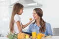 Little girl giving an orange segment to her mother in the kitchen Stock Photo