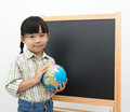 Little girl with globe children educational concept holding in fornt of the blackboard Royalty Free Stock Images
