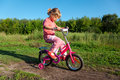 Little girl goes for drive on bicycle in park Royalty Free Stock Photo