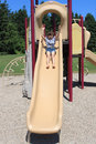 Little girl going down a slide Royalty Free Stock Photo