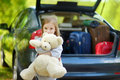 Little girl going to a car vacation adorable with big teddy bear leaving for with their parents Stock Images