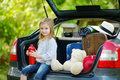 Little girl going to a car vacation adorable with big teddy bear leaving for with their parents Royalty Free Stock Photography